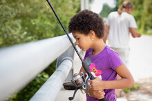 Pretty Child With Short Curly Kinky Hair Looking Out At The Water While She Fishes