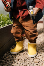 Crop Boy With Tools In Hothouse