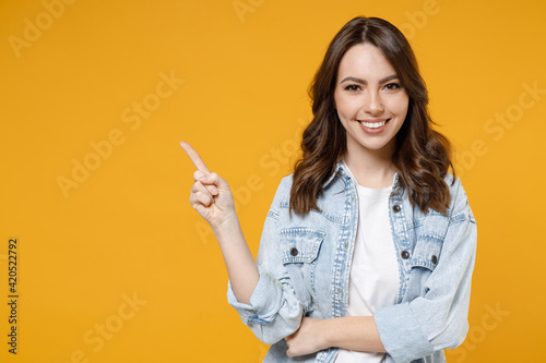 Obraz Young smiling woman promoter in denim shirt white t-shirt recommend suggest select advert point index finger aside on workspace commercial promo area mock up copy space isolated on yellow background. - fototapety do salonu