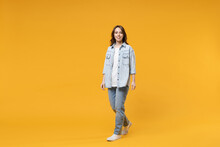Full Length Of Young Caucasian Smiling Happy Confident European Cute Woman 20s Wearing Stylish Casual Denim Shirt White T-shirt Walking Going Look Camera Isolated On Yellow Background Studio Portrait