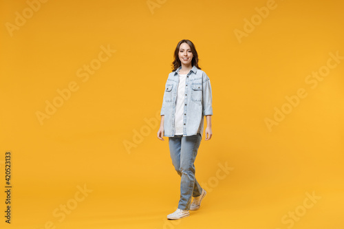 Obraz Full length of young caucasian smiling happy confident european cute woman 20s wearing stylish casual denim shirt white t-shirt walking going look camera isolated on yellow background studio portrait - fototapety do salonu