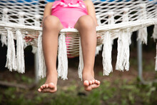 Closeup Of A Pretty Toddler Child's Toes As She Sits Happily In A Crochet Yarn Hammock.