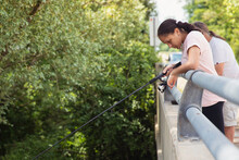 Portrait Of A Teen Girl Peering Over A Ledge As She And Her Grandfather Fishes