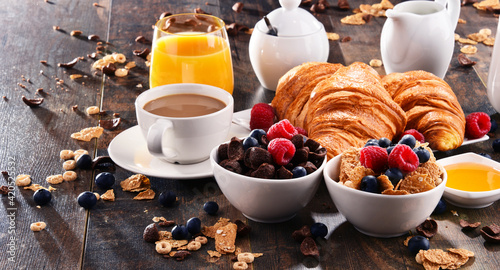 Fototapeta Breakfast served with coffee, juice, croissants and fruits obraz