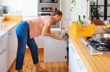 Woman Throwing Plastic Bottle Into Bin In Kitchen
