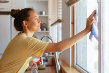 Young Woman Cleaning Window In Kitchen