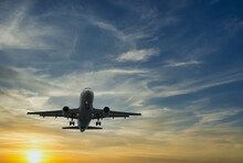 The Plane Against The Blue Sunset Sky. The Setting Sun. Sunset. Landscape With Aircraft Is Flying In The Blue Sky With Orange And Pink Clouds. The Plane Blue Sunset Sky