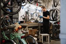 Man Working In Repair Shop Of Bicycles