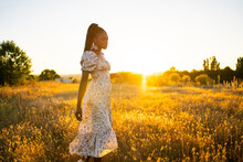 Black Woman Walking On A Landscape Field At Sunset In Summer.