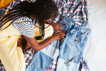 Anonymous Ethnic Teenager Applying Patch On Jeans