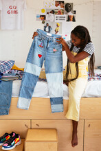 Cheerful Black Teenager Showing Stylish Jeans