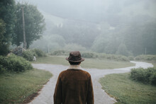 Anonymous Man At A Crossroads On A Foggy Day
