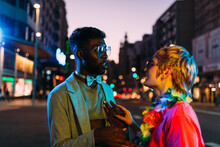 Multiracial Couple Talking In City Street At Night