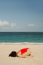 A Curly Girl In A Red Bathing Suit Lies On The Beach.
