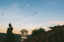 Rooftop View On A Spanish House With Birds In The Evening Sky With The Sun Settting And Moon Rising
