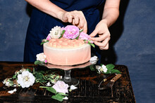 Women Decorate The Cake With Fresh Flowers