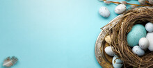 Happy Easter Concept. Frame Of Easter Eggs And Spring Flowers On Blue Background. Flat Lay, Top View, Copy Space.