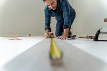 Close Up Of Man Measuring The Floor To Install Wooden Decking In His House