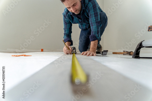 Obraz close up of man measuring the floor to install wooden decking in his house - fototapety do salonu