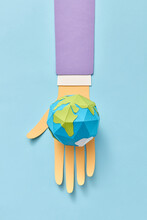 Papercraft Earth's Globe On A Paper Man's Hand.