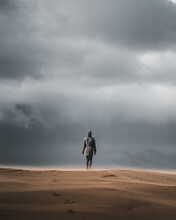 Vertical Shot Of An Unrecognizable Woman Walking By A Sandy Path On A Hi