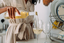 Woman Pouring Wine Into Glasses At Home