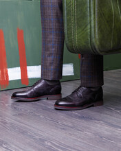 Man In Classic Leather Shoes, With A Vintage Suitcase In Hand On A Green Background