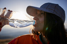 Woman Consuming Drink In Mountains.
