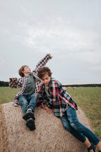Two Brother Sitting On A Haystack In The Field.