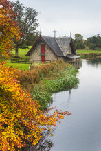 Boat House By The Lake With Colourful Trees In The Foreground