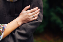 Bride's Hand With Wedding Ring On Groom's Uniform. Close Up.