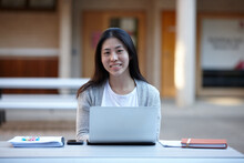 Young Chinese University Student Studying At Table Outdoors With Laptop