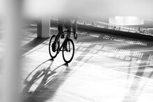 Cyclist Urban Bike Racer In Car Park Environment, Monochrome Contrast Light And Shadows On Ground Silhouette