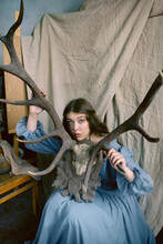 Portrait Of A Beautiful Woman Dressed In An Old Fashion Dress And Holding Deer Horns