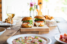 Wild Salmon Burgers On Rustic Wooden Dinner Table.