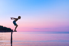 Boy About To Jump Into Calm Lake At Dusk From A Dock At Family Cottage