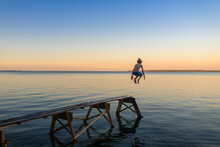 Boy Jumping Into Lake From Dock On Calm Lake At Sunset At Family Cottage