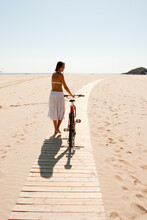 Young Woman Portrait With Bike At The Beach
