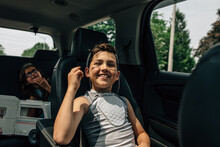 Boy Riding Home In Car After Baseball.