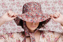 Young Woman Adjusting Summer Hat