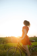 Girl In A Red Dress On A Retro Bike On A Sunset Background