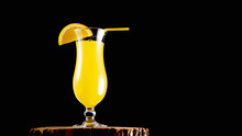 Alcoholic Cocktail With A Straw On A Black Background. Yellow Lemonade In A Glass On A Wooden Board. Fruit Drink.