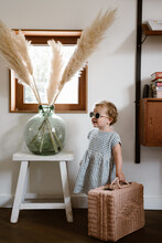 Little Girl Wearing A Striped Dress And White Sunglasses With Rotan Suitcase Ready For A Staycation