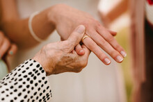 Close Up Of Grandma Holding Hand Of Bride With Golden Wedding Ring