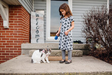 Young Girl Walking White And Gray Cat On Leash.