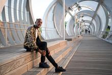 Young Black Man Sitting On A Pedestrian Bridge.
