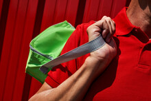 Man In Red Carrying A Green Cooler Bag