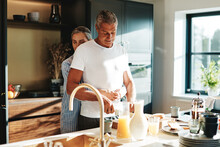 Woman Hugging Her Husband Making Breakfast