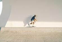 Ethnic Skater Riding Skateboard On Border