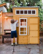 Boy Reaching Into Playhouse Mailbox